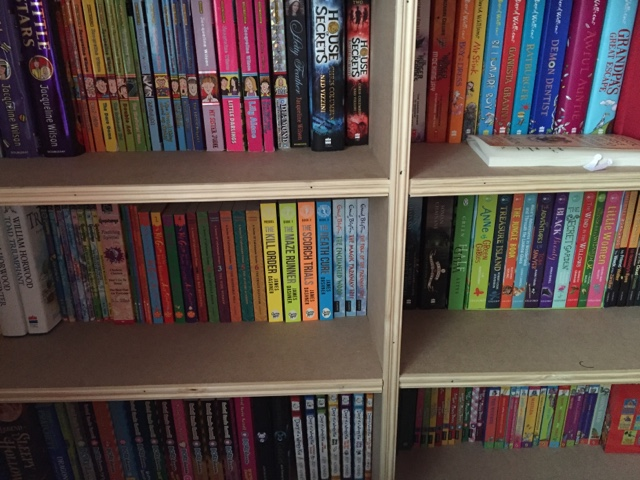 bookshelf with books in rainbow order
