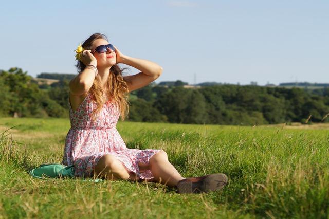 girl sitting in summer meadow