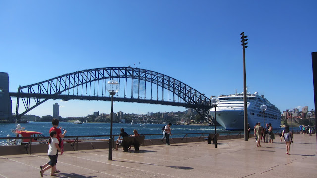 A large cruise ship by the Sydney Harbour Bridge.