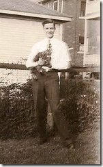 GOULD_Harry Norman_standing in a yard holding his cat_circa 1930_cropped
