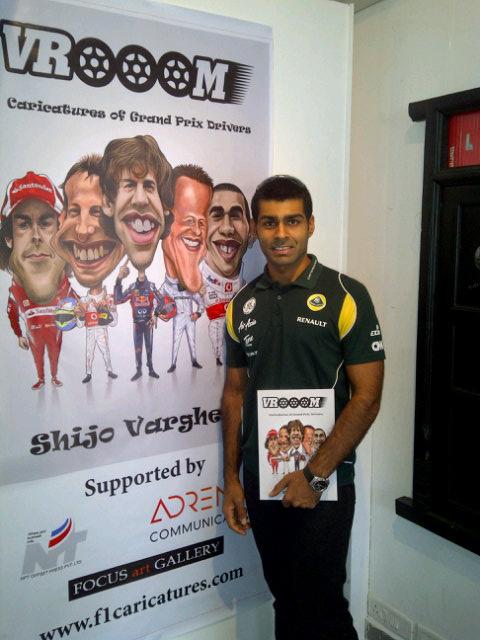 Карун Чандхок на фоне плаката VROOOM на Гран-при Индии 2011