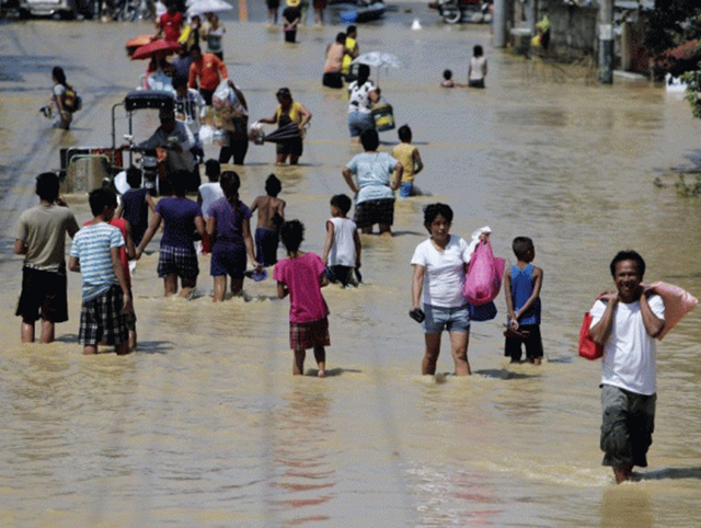 Filipino villagers wade at the flood-hit town of Calumpit, Bulacan province, northern Manila, in the Philippines, after Typhoon Koppu, 21 October 2015. Photo: The Independent