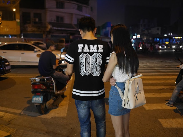 "young man wearing shirt with ""FAME 08"" on the back with a young woman"