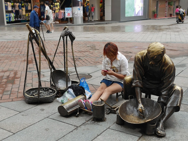 woman checks here mobile phone while sitting on a sculpture's small stool