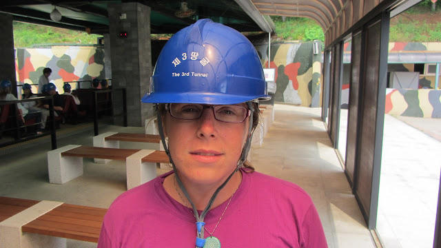 Heather with hard hat ready to enter the Third Infiltration Tunnel. A monorail, visible at left, takes visitors 300 m into the tunnel.