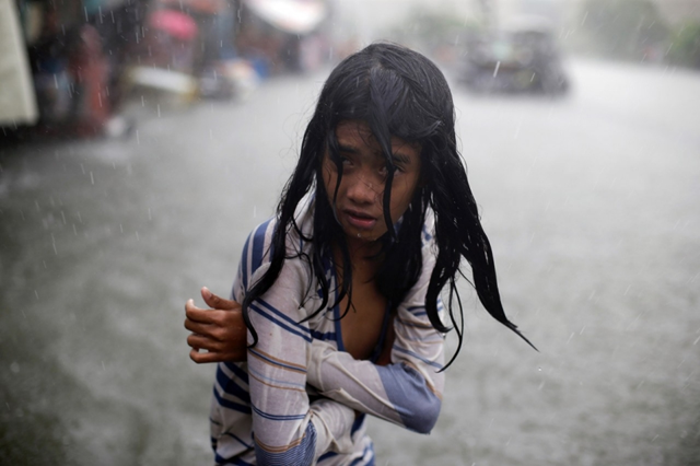 A Filipino girl tries to keep herself warm as she wades in floodwaters in Malabon, 8 July 2015. Photo: Aaron Favila / AP
