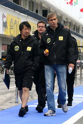 Виталий Петров идет по пит-лейну с Аяо Комацу и ест яблоко на Хунгароринге на Гран-при Венгрии 2011