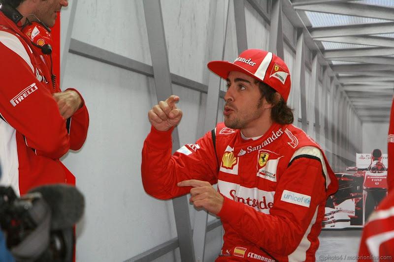 Фернандо Алонсо показывает что-то механику в боках команды Ferrari на Гран-при Германии 2011