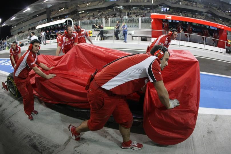 механики Ferrari толкают болид Фернандо Алонсо по пит-лену на Гран-при Абу-Даби 2011
