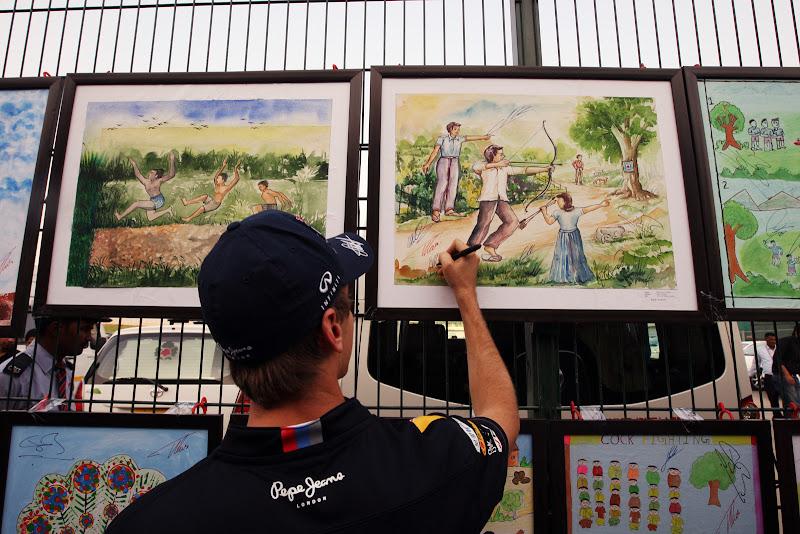 Себастьян Феттель ставит автограф на рисунках индийских школьников на Гран-при Индии 2011