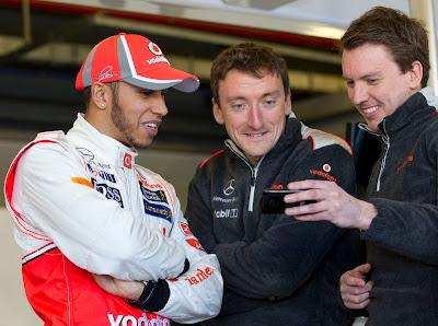 механики McLaren показывают что-то забавное на телефоне Льюису Хэмилтону на предсезонных тестах 2012 в Барселоне 21 февраля 2012