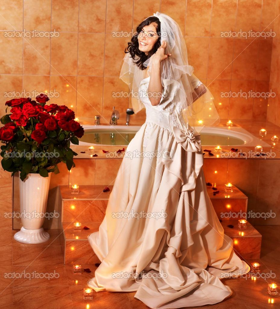 Woman in wedding dress relaxing in bath tube.