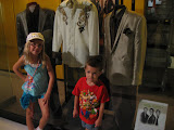 Hannah and Bryan standing by suits that members of Rascal Flats wore in the Country Music Hall of Fame in Nashville TN 09042011