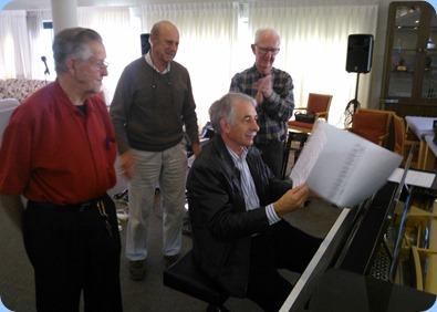 Members gather around Claude Moffat playing the Schimmel mini-grand piano