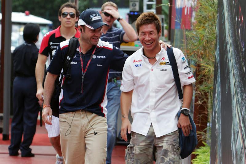 смеющиеся Рубенс Баррикелло и Камуи Кобаяши идут по паддоку Гран-при Сингапура 2011