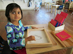 """In our preschool program, children learn to write using hands-on materials. Here, a young girl has been tracing the Montessori Sandpaper Letters, and is now """"writing"""" letters in a tray full of sand."""