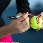 Agnieszka Radwanska signs a tennis ball