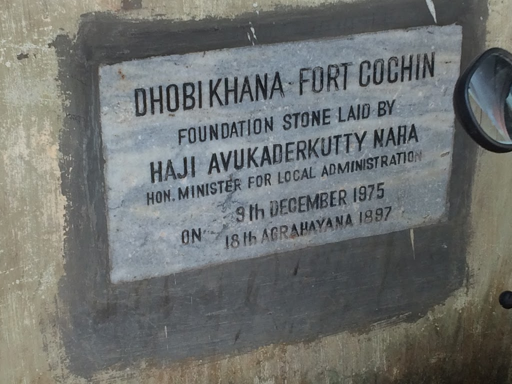 This plaque is at the entrance of the Dhobi Khana Public Laundry in Fort Cochin (Kochi). The place is a coop laundry with a building set for ironing laundry, another with