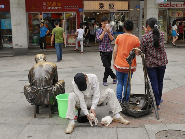 man sitting on a sculpture's small stool while attending to two puppies; other people have their photograph taken with the scullpture