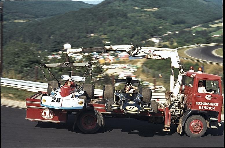 Марк Донохью и Джон Уотсон в болидах March и Lotus едут на грузовике по Нюрбургрингу на Гран-при Германии 1975