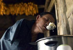 Chen Xingyin mengambil nasi dengan sendok di mulutnya