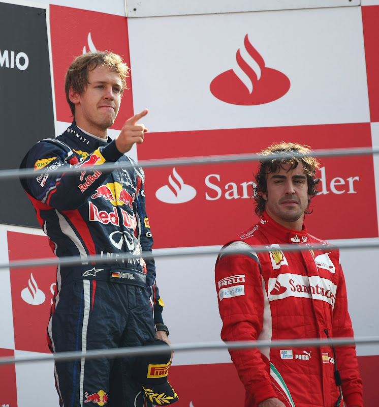 Себастьян Феттель показывает палец на фоне Фернандо Алонсо на подиуме Гран-при Италии 2011 в Монце