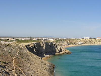 Utsikt mot en by som ligger over en strand.