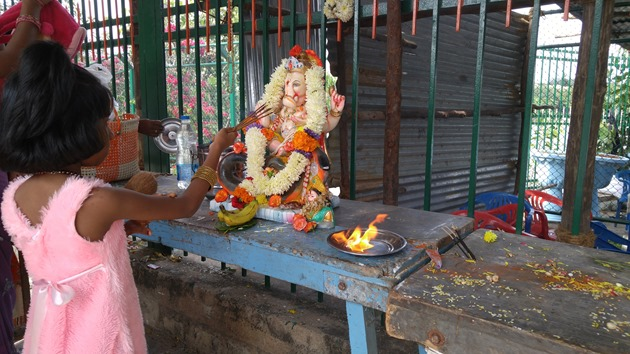 Small girl offering prayers to Ganesha and Gauri just before immersion in Bangalore lake