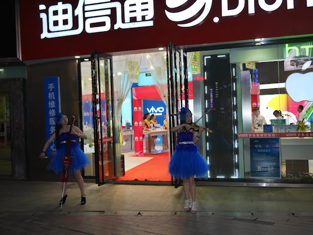 two young women in blue dresses playing electric string instruments outside a mobile phone store in Changsha