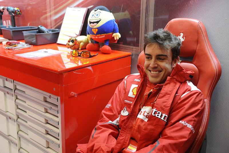 улыбающийся Фернандо Алонсо и его талисманы в боксах Ferrari на Гран-при США 2012