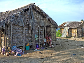 The King's main hut with his wife and several of his children sitting in the doorway.