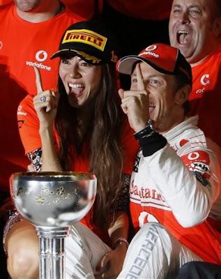 Джессика Мичибата и Дженсон Баттон показывают палец на Гран-при Японии 2011
