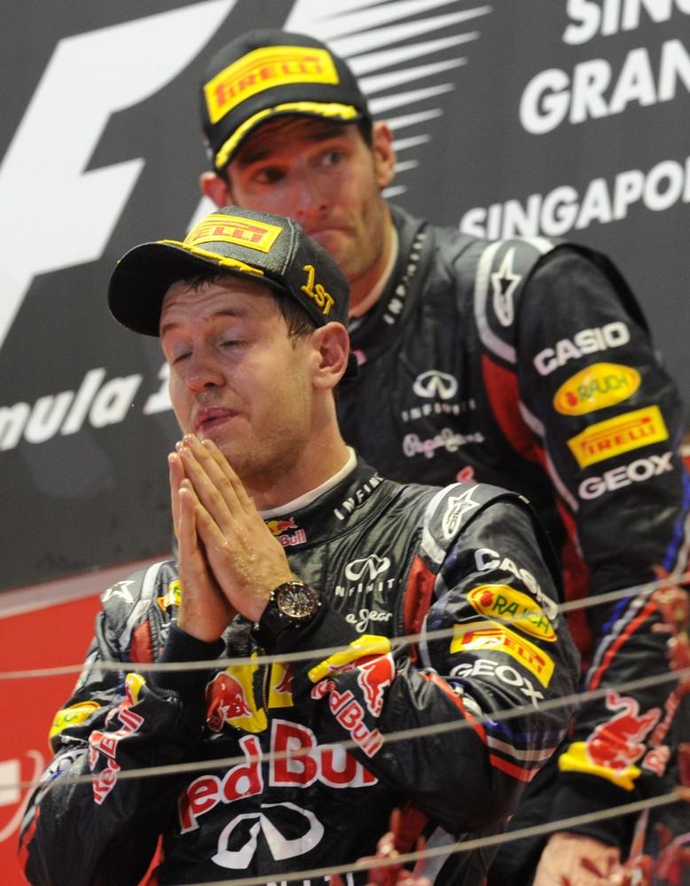 молящийся Себастьян Феттель и Марк Уэббер позади на подиуме Гран-при Сингапура 2011
