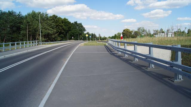 Na wiadukcie pozostawiono miejsca na drogę dla rowerów. Skręcamy w prawo w drogę serwisową, choć znak informuje, że droga jest ślepa.