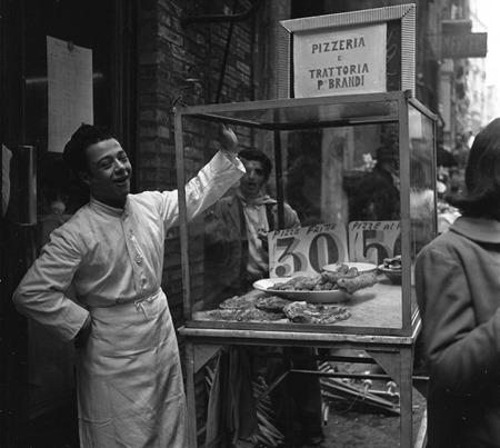Strade di Napoli: biancheria stesa ai balcon, venditore di pizza al mercatino