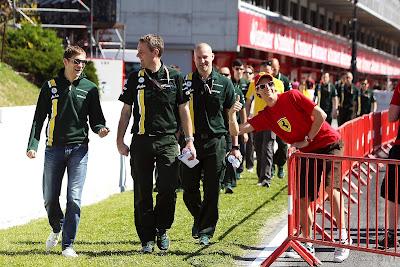 болельщик Ferrari фотографирется на фоне Виталия Петрова и механиков Caterham на Гран-при Испании 2012
