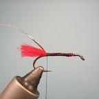 1. Do haczyka przywiązuję chwościk z czerwonej włóczki. Jako owijka posłuży srebrna pleciona lameta.