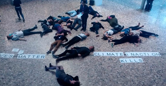 Climate activists inside the entryway of the UN-sponsored talks in Bonn, Germany as they staged a die-in to highlight the millions of lives that will be lost or impacted by continued government inaction on human-caused global warming. Photo: FOE / Twitter / @FOEEurope
