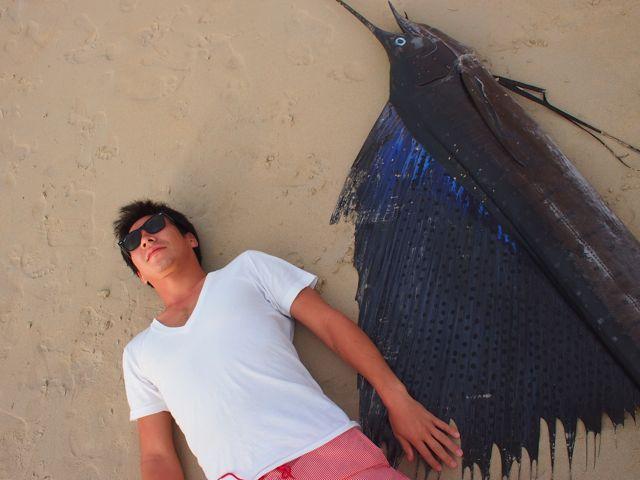 Камуи Кобаяши лежит на песке рядом с рыбой-меч
