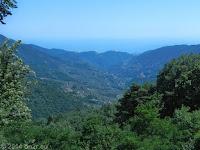 Von Molini di Triora Richtung Vignai/Bajardo: Auf der waldreichen, schmalen und unübersichtlichen SP75 über den Monte Ceppo. Im Dunst das Mittelmeer und hinter den Hügeln San Remo an der Riviera di Ponente.
