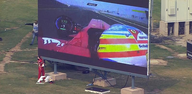 Фернандо Алонсо смотрит повтор тв трансляции на экране автодрома на Гран-при Индии 2011