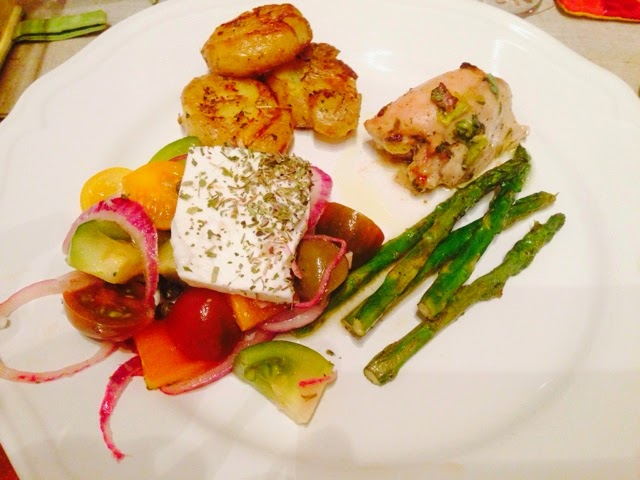 Plate of authentic Greek salad, oregano chicken, roast potatoes and asparagus
