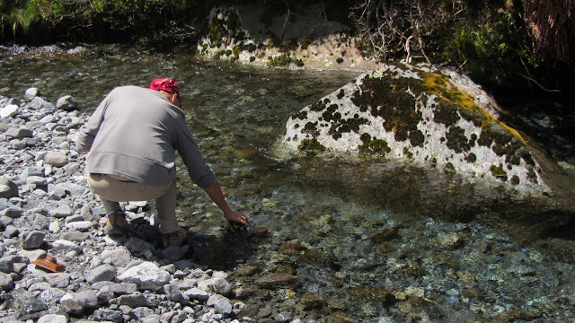 Erik filling a water bottle from a glacial stream - ready to drink!