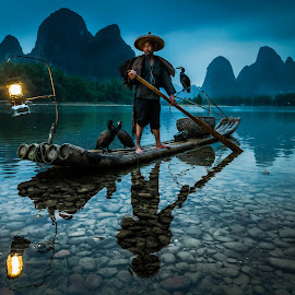Warrior by Andy Beales - People Street & Candids ( environmental portrait, china travel, blue hour, li river, guilin fishermen, guilin china, travel, people, guangxi, bamboo raft, li, cormorant fishing, asia, lamp, cormorant fisherman, raft, guilin, travel photography )