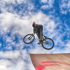 by Marco Bertamé - Sports & Fitness Other Sports ( clouds, wheel, speed, dow, stunt, jump, ramp, bicycle, flying, two, red, sky, blue, cloudy, brown, air, high )