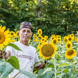 Natural man in sunflower garden by Todd Crenshaw - People Portraits of Men ( smoking, male, sunflower, garden, man )
