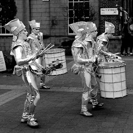 Silver Drums by DJ Cockburn - People Musicians & Entertainers ( monochrome, street performance, black and white, se18, silver, drummer, road, grayscale, england, london, woolwich, no 1 street, percussion, royal arsenal, tall ship festival, duke of wellington avenue, musician, crossroads, river thames )