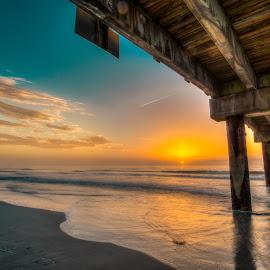 Sunrise under the pier by Tim Hancock - Landscapes Sunsets & Sunrises ( clouds, sand, waves, pier, ocean, beach, sunrise, pilings )