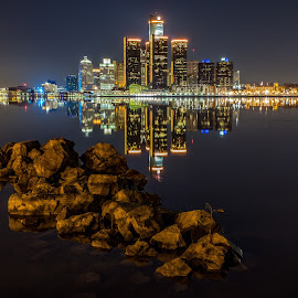 Uncommon Tranquility by Steve Biro - City,  Street & Park  Skylines ( #detroitriver #detroit #windsor #reflection #rocks #nightscapes #calm #peaceful #tranquil #rencen #renaissance #landscape #cityscape #waterfront #photooftheday )