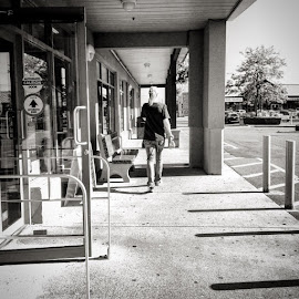 The Talk by Ernie Kasper - Instagram & Mobile iPhone ( walking, person, building, store, black and white, candid, concrete, shadows, lights, overhang, glass, bnw_society, cell phone, bnw_capture, bnw, sidewalk )
